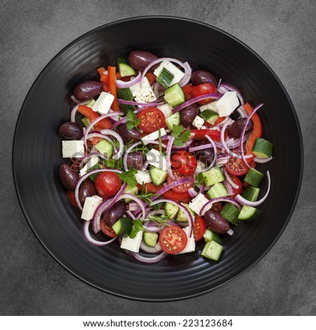 Greek salad on black plate over dark slate.  Overhead view. - stock photo