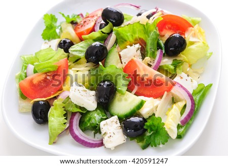 Greek salad with cheese in plate isolated on white