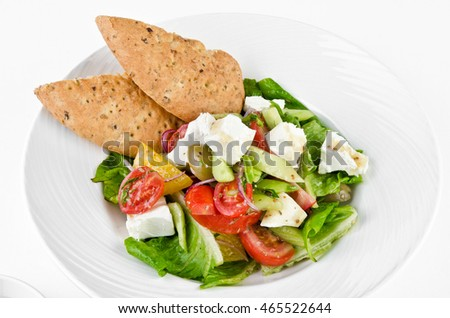 Greek salad with feta cheese, Ligurian olives and tortilla pea and hummus on a plate on a white background, closeup