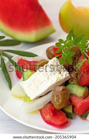 Greek salad with feta cheese, olives and basil