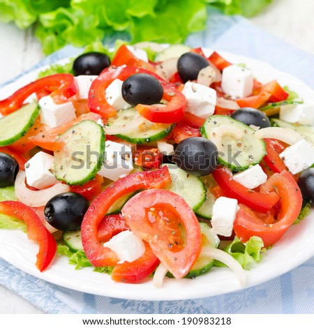 Greek salad with feta cheese, olives and vegetables on a plate, close-up