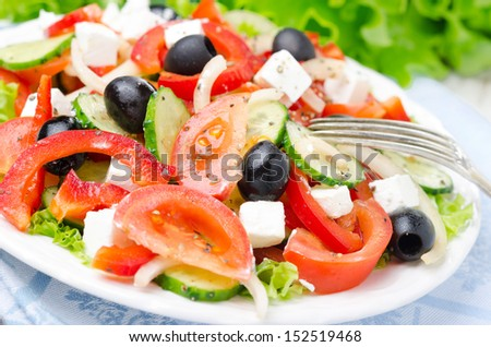 Greek salad with feta cheese, olives and vegetables on a plate, horizontal closeup