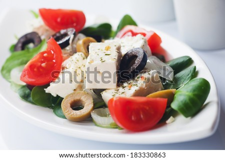 Greek salad with feta cheese, olives, cherry tomato and onion