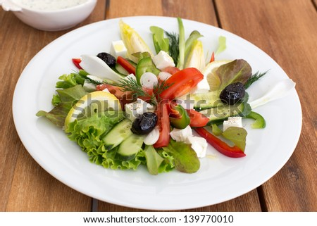 Greek salad with feta, tomatoes, cucumber, peppers and black olives. With bowl of sauce on a wooden table.