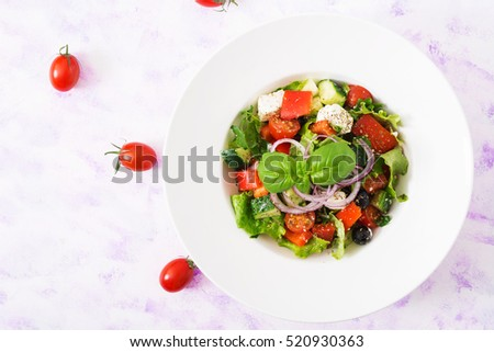 Greek salad with fresh tomato, cucumber, red onion, basil, lettuce, feta cheese, black olives and Italian herbs. Top view