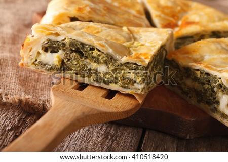 Greek spanakopita piece of pie on the table macro. horizontal