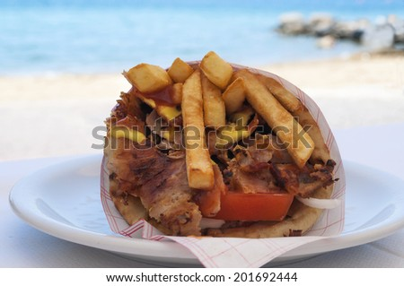 Greek specialty - giros, with beach and sea in the background - stock photo