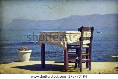 Greek specific - Vintage photo of dining table and chairs set outside on a beach  - stock photo