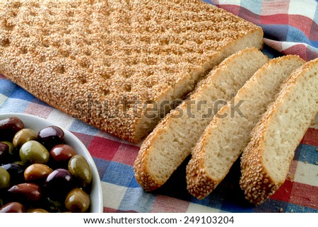 Greek traditional bread and olives on checkered table cloth. - stock photo