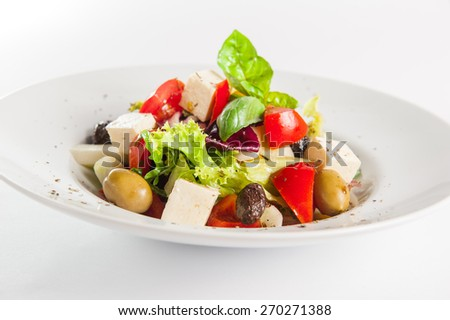 Greek Vegetable salad with feta cheese, olives, cucumbers, tomatoes, pepper  on the white plate isolated om white background