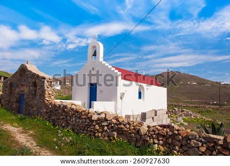 Greek white church surrounded by flowers on the island - stock photo