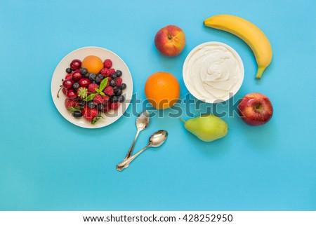 Greek yogurt around orange, banana, pear, peach, apple, plate of strawberries, raspberries, blueberries and 2 spoons on light blue background.  Yogurt and fruits, berries as an ingredients. Top view. - stock photo