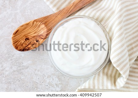 Greek yogurt in a bowl, downward view with cloth and spoon on a white marble