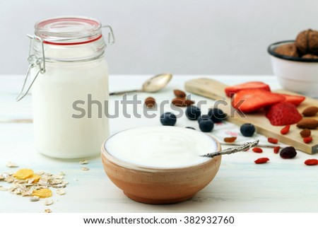 Greek yogurt in a ceramic bowl with spoons on wooden background - stock photo