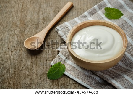 Greek yogurt in a wooden bowl with spoons on wooden background - stock photo