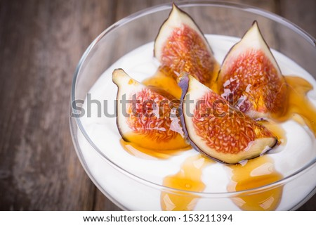 Greek yogurt with figs and honey, in a glass bowl over old wood background. Vintage effect with intentional vignette - stock photo