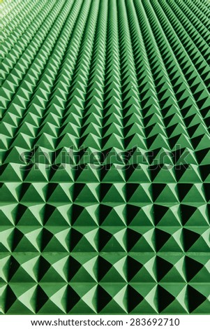 Green abstraction perspective on a wall composed of blue bricks with sun shades - stock photo