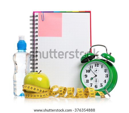 Green alarm clock, apple, bottle of water and measuring tape with blank notebook as concept of diet - isolated on white  - stock photo