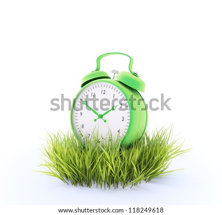 Green alarm clock in a patch of grass - stock photo