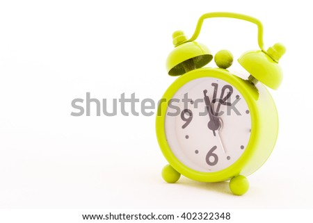 Green alarm clock on white background.