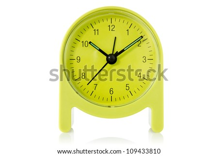green alarm clock over a white background