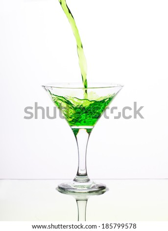 Green alcohol cocktail in martini glass with splash on white background - stock photo