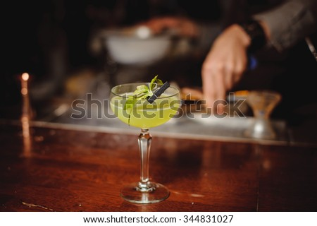Green alcohol cocktail with lime in bar