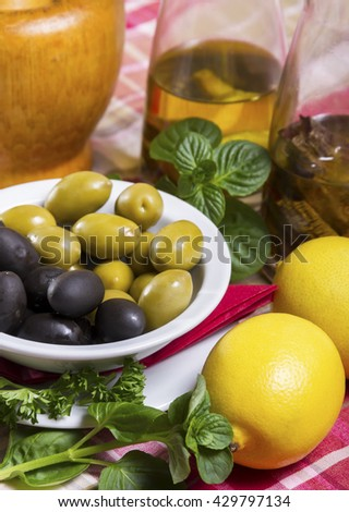 Green and black olives in a white bowl with a saucer, spicy olive oil in glass bottles, lemon and basil placed on the table. - stock photo