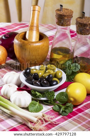 Green and black olives in a white bowl with a saucer, spicy olive oil in glass bottles with dispenser, wooden mortar and pestle, lemon, garlic, basil, onion and spring onion placed on the table. - stock photo