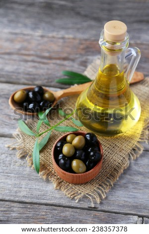 Green and black olives in bowl on grey wooden background - stock photo