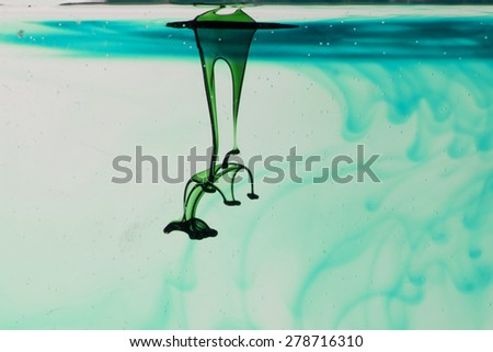 Green and blue liquid in water making abstract forms - stock photo