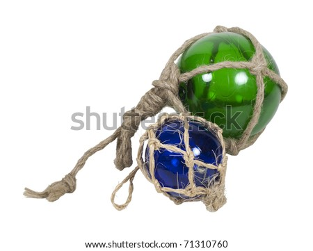Green and blue nautical glass floats tied with rough rope - path included - stock photo