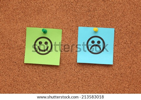 Green and blue paper with happy and sad faces on corkboard (bulletin board). - stock photo
