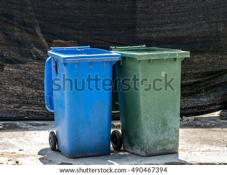 Green and blue Trash can on concrete floor