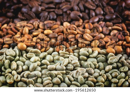 Green and brown decaf unroasted and black roasted coffee beans as background. - stock photo