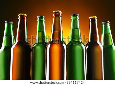 Green and brown glass bottles of beer on dark lighted background, close up