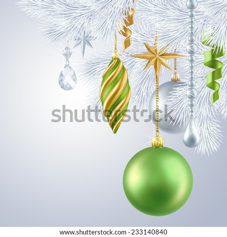 green and gold ornaments hanging on frozen silver Christmas tree, winter holiday background  - stock photo