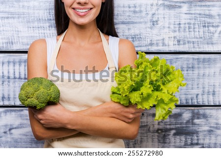 Green and healthy food. Cropped image of beautiful young smiling woman in apron holding fresh lettuce and broccoli while standing in front of wooden background - stock photo