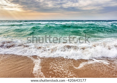 green and mighty sea wave attacks the sandy beach and break on them