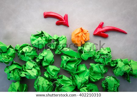 green and orange crumpled paper balls  with red arrow business idea concept.jpg - stock photo
