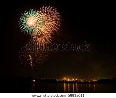 Green and Orange Fireworks at lake on King Birthday Festival and Holiday in Thailand. - stock photo