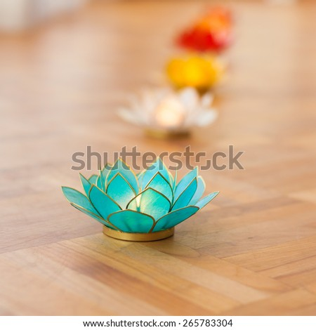Green and other lotus candles on wooden floor - stock photo