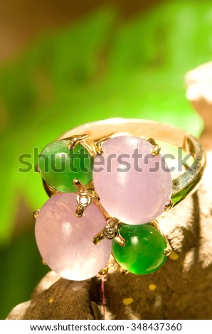 Green and pink jade gold ring with beautiful background. - stock photo