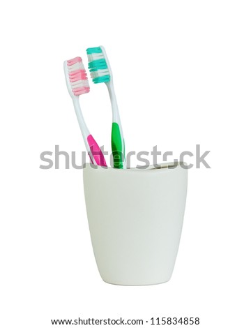 green and pink tooth brush side to side closeup in white ceramic cup in white background