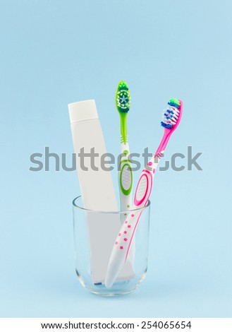 Green and pink toothbrushes and white toothpaste in glass cup isolated on blue background - stock photo