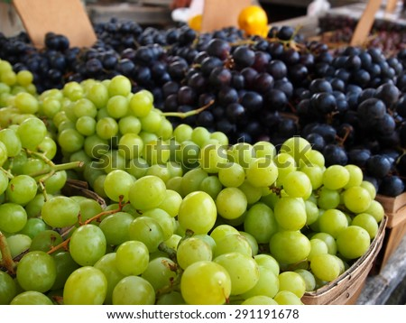 Green and purple bunches of grapes in baskets for sale at local farmer's market. - stock photo