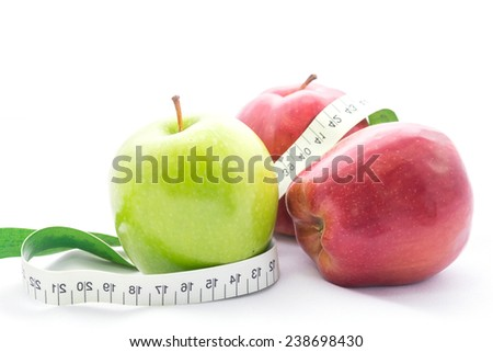 Green and red apple wrapped with a tape measure,on white background - stock photo