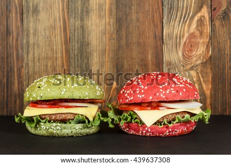 Green and red cheeseburgers on wood background close-up