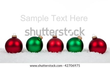 Green and red Christmas ornaments/baubles on a white background with copy space - stock photo