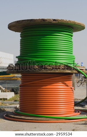 Green and red electricity cable on wooden spools on construction area. Focus on the spools.